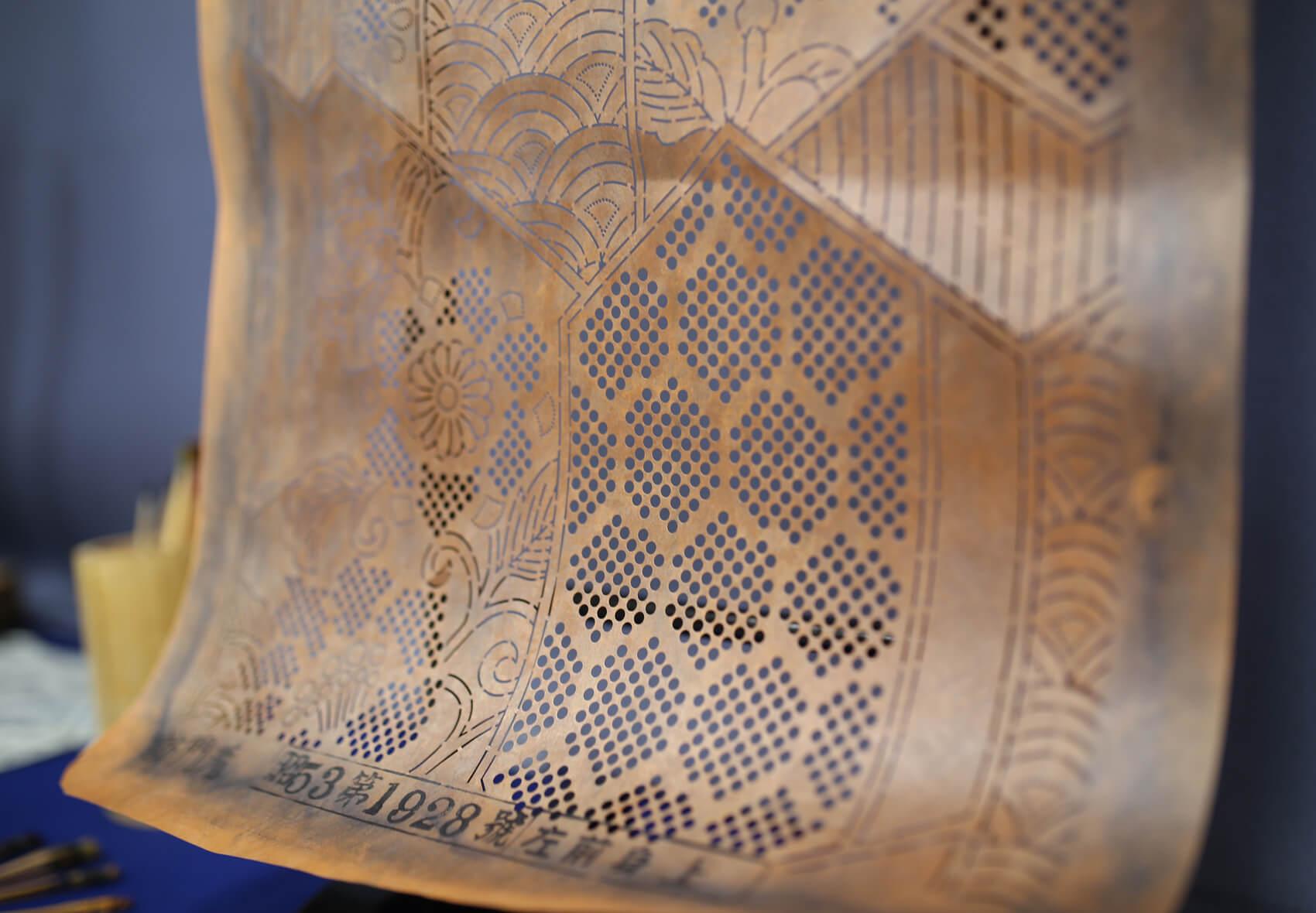 型紙。下絵に従って絞る部分を実寸の方眼紙に落とし込み、その後、和紙を柿渋に何度も浸した型紙に写して彫刻刀のような道具で彫っていきます。