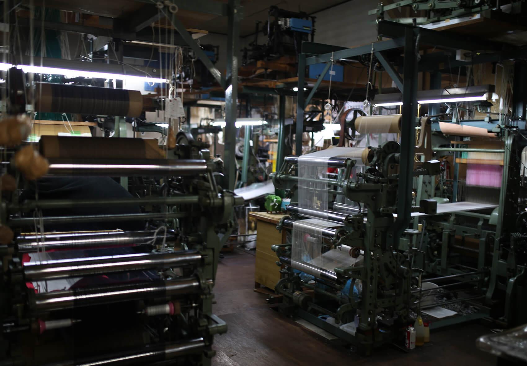 機械織機が並ぶ1階。機械織りは工夫が早いスピードで進むのが大きな利点と言います。